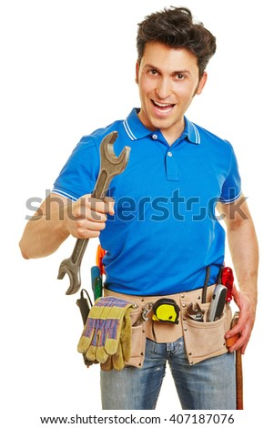 Smiling handyman holding a wrench and carrying a tool belt - stock photo