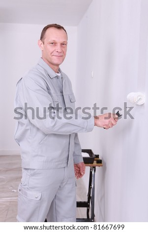 Smiling handyman painting a room white - stock photo