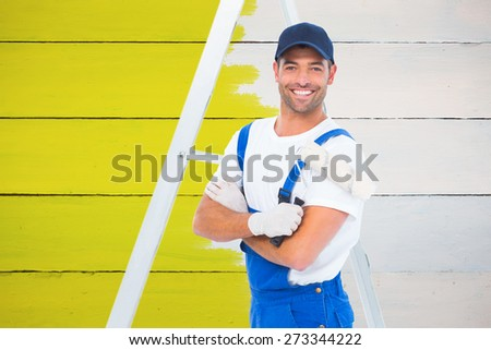 Smiling handyman with paint roller standing by ladder against painted blue wooden planks - stock photo