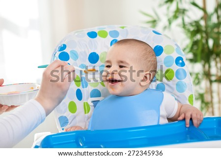 Smiling happy baby child enjoy eating lunch - stock photo