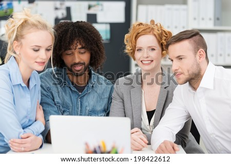 Smiling happy beautiful businesswoman working with her three colleagues in the office sitting together sharing a laptop computer