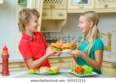 smiling happy boy and girl holding homemade hamburgers or sandwiches - stock photo
