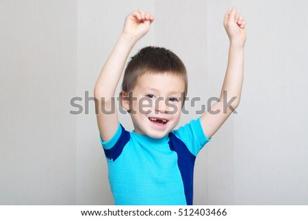 smiling happy boy greeting with hands up, toothless child