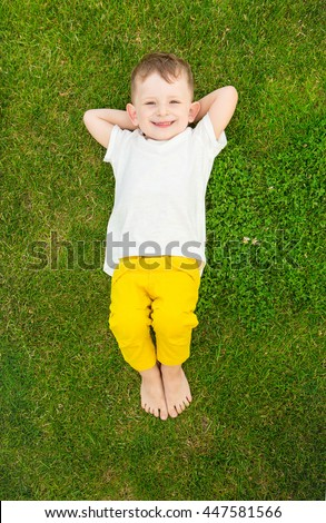 Smiling happy boy relaxing on green grass. Summer time weekend mood. Templates t-short no print, you can place your own print or text.  Top view