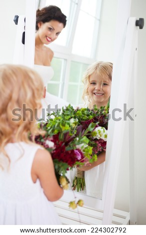 Smiling happy bride and a flower girl indoors. Vertical shot - stock photo