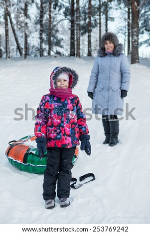 Smiling happy child with mature mother while tubing in winter forest - stock photo