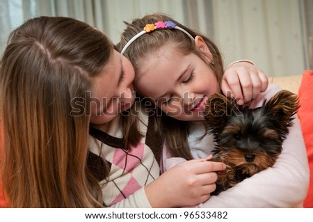 Smiling happy children playing with little dog - stock photo