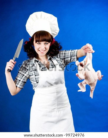 Smiling happy cook woman holds a Crude hen and knife - stock photo