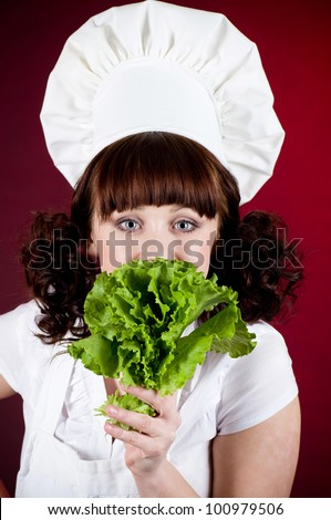 Smiling happy cook woman with green salad - stock photo