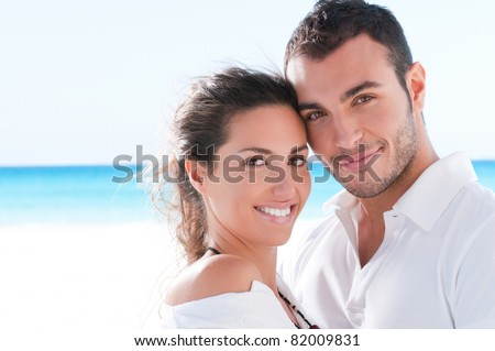 Smiling happy couple looking at camera together at summer beach - stock photo