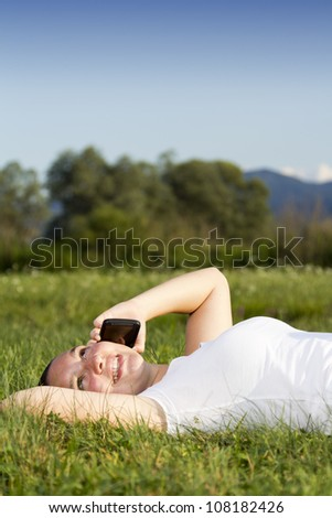 Smiling happy cute girl lying on the grass and talking on tablet phone - stock photo