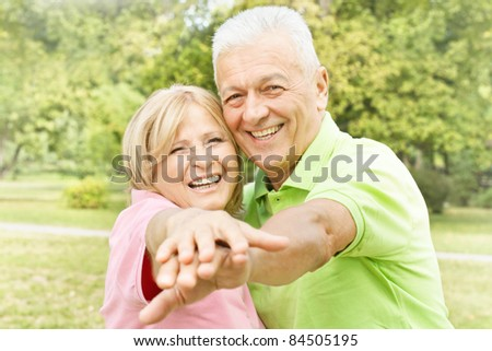 Smiling happy elderly couple enjoying outdoors. - stock photo