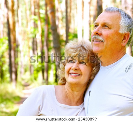 Smiling happy  elderly couple in the summer forest - stock photo