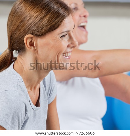 Smiling happy elderly woman exercising in gym