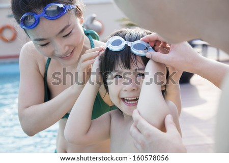 Smiling happy family helping son put on goggles by the poolside - stock photo