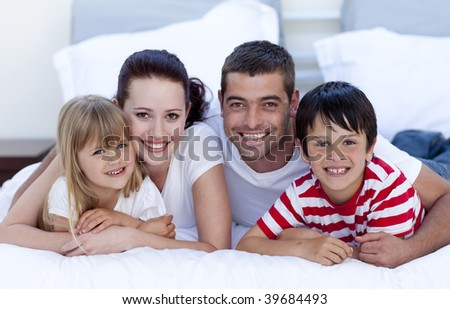 Smiling happy family lying in bed together - stock photo
