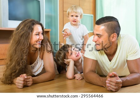 Smiling happy family of four enjoying time in living room at their home - stock photo