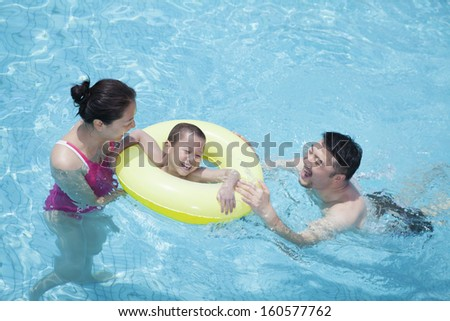 Smiling happy family playing in pool with their son in inflatable tube - stock photo