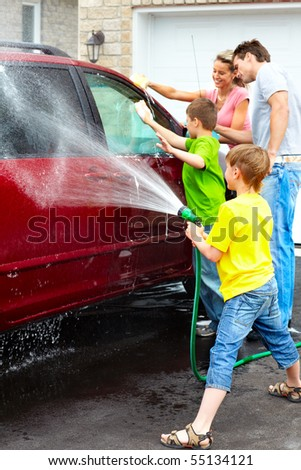 Smiling happy family washing the family car - stock photo