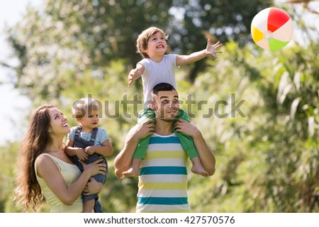 Smiling happy family with little daughters playing with ball outdoor - stock photo