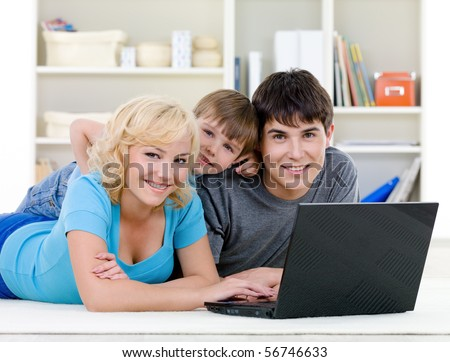 Smiling happy family with son lying together and using laptop at home - indoors - stock photo