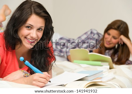 Smiling happy female students preparing for exam - stock photo