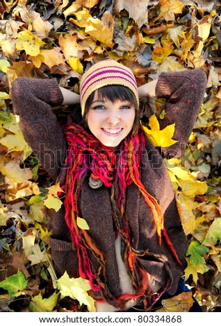 Smiling happy girl lying in autumn leaves. Outdoor. - stock photo