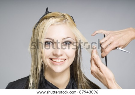 Smiling happy hair client or customer while hairdresser cutting hair - stock photo