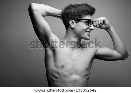 Smiling happy handsome and muscular male model with nice body wearing trendy glasses and posing over light-gray background with hands up. Hipster style. Copy-space. Black & white studio portrait.