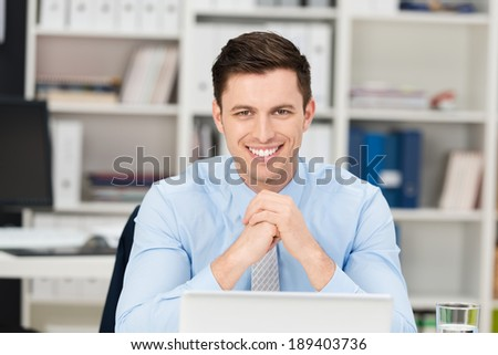 Smiling happy handsome young businessman sitting at his desk looking at the camera with a beaming friendly smile - stock photo