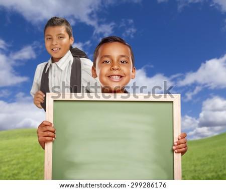 Smiling Happy Hispanic Boys In Grass Field Holding Blank Chalk Board. - stock photo