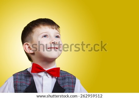 Smiling, Happy, Joyful beautiful little boy, looking up.Close-up Studio Portrait isolated on yellow background.