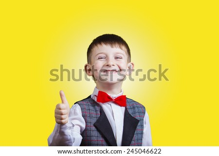 Smiling, Happy, Joyful beautiful little boy with thumb up, looking at camera.Close-up Studio Portrait isolated on yellow background.
