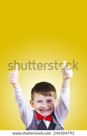 Smiling, Happy, Joyful beautiful little boy with thumb up, looking at camera.Close-up Studio Portrait isolated on yellow background. - stock photo