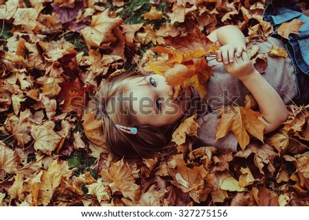 Smiling happy little girl portrait, lying in autumn leaves. Outdoor - stock photo