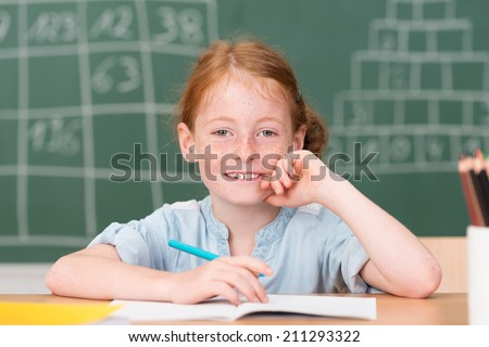 Smiling happy little schoolgirl in class sitting at her desk n front of the blackboard grinning at the camera - stock photo