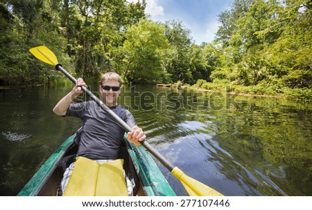 Smiling, happy man kayaking along a beautiful jungle river. Lots of copy space in an active outdoor lifestyle photo - stock photo