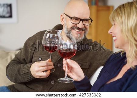 Smiling happy middle-aged couple toasting each other with glasses of red wine as they look lovingly into each others eyes - stock photo