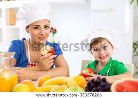 Smiling happy mother and child enjoy and eating fruits in kitchen