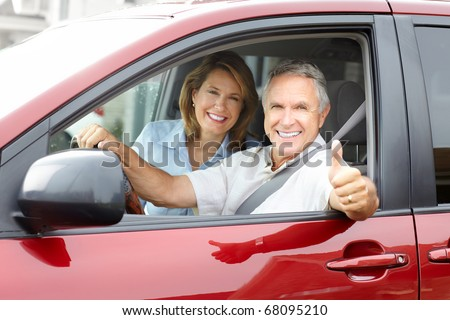 Smiling happy senior couple in the car - stock photo