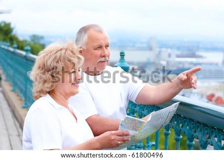 Smiling happy senior couple in the city - stock photo