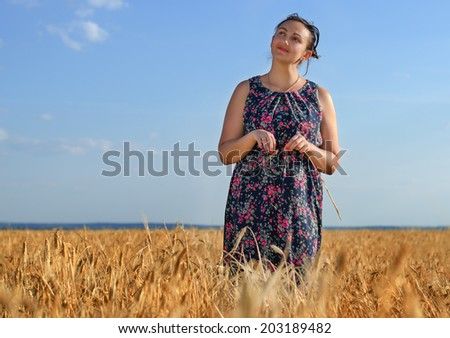 Smiling happy tanned middle-aged woman standing against a sunny blue summer sky in a golden field of wheat with copyspace - stock photo