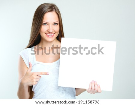 smiling happy woman holding  blank paper. empty copyspace for ads. - stock photo