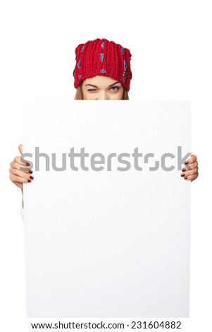 Smiling happy woman in winter hat peeking out of the edge of white banner and winking over white studio background - stock photo