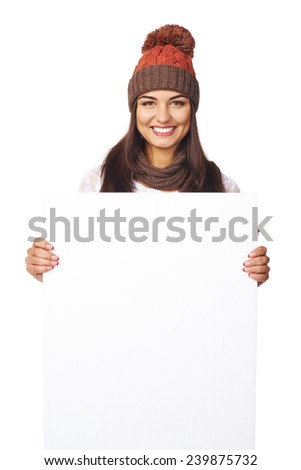 Smiling happy woman in winter hat peeking out of the edge of white banner over white studio background - stock photo