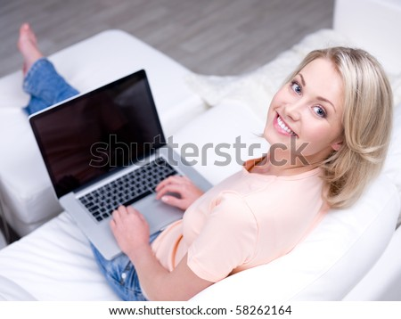 Smiling happy woman sitting on the sofa and using laptop - High angle view - stock photo
