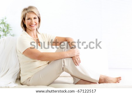 Smiling happy  woman sitting on the sofa at home - stock photo