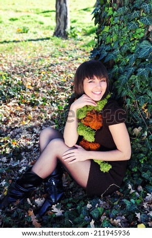 Smiling happy woman sitting under a tree in the autumn park. - stock photo