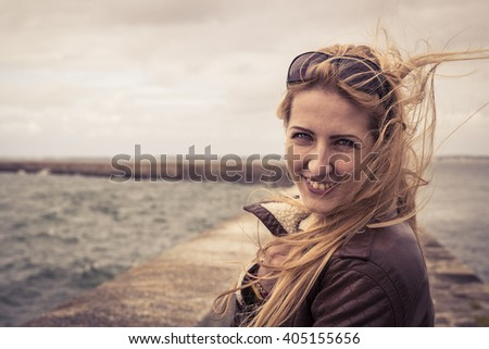 Smiling happy woman standing near the gate, looking back, stormy sea background, warm colors - stock photo