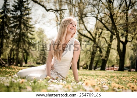 Smiling happy young person (teenager) sitting outdoors in blooming grass and looking away - stock photo